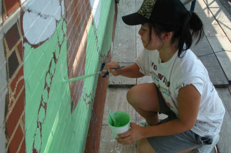 The team devoted much of its planning process to visiting social justice organizations and interviewing people committed to creating change across diverse fields. Here, a youth puts this research into motion with paint.